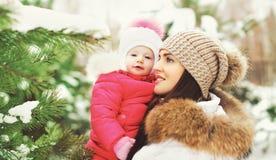 Moeder en kind in de winterbos dichtbij Kerstmisboom Royalty-vrije Stock Afbeeldingen