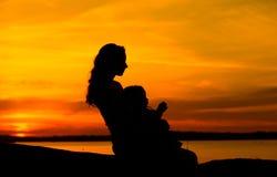 Moeder en kind die de zonsondergang bekijken stock foto