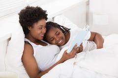 Moeder en Kind die een Boek in Bed lezen stock afbeeldingen