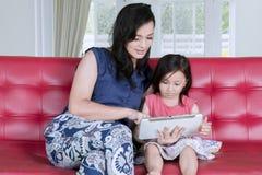 Moeder en kind die een tablet op de laag gebruiken royalty-vrije stock foto's