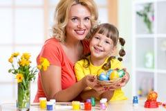 Moeder en kind die geschilderde paaseieren tonen Stock Afbeeldingen
