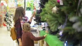 Moeder en Kind die Kerstboom in de Supermarkt kiezen Het jonge Mooie Mamma en de Dochter kopen Kerstmis-Boom met stock footage