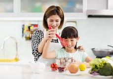 moeder en kind die in keuken koekjes voorbereiden stock foto
