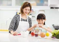 moeder en kind die in keuken koekjes voorbereiden stock foto's