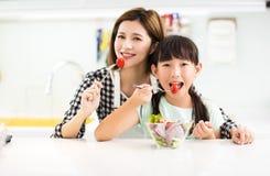 Moeder en kind die in keuken salade eten royalty-vrije stock afbeelding