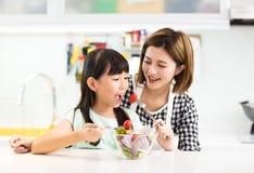 Moeder en kind die in keuken salade eten stock afbeelding