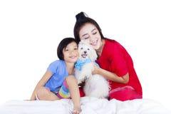 Moeder en kind die Maltees puppy omhelzen Royalty-vrije Stock Afbeeldingen
