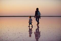 Moeder en kind die op een zout en pekel van een roze die meer lopen, door het zoutmeer van micro-algendunaliella wordt een gekleu Royalty-vrije Stock Foto's