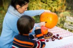 Moeder en kind die pompoen voorbereiden op Halloween Royalty-vrije Stock Fotografie
