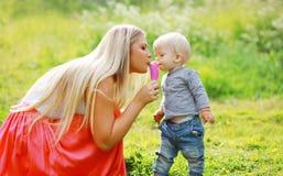 Moeder en kind die roomijs in openlucht in de zomer eten Stock Foto