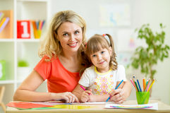 Moeder en kind die samen thuis schilderen Stock Foto