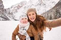 Moeder en kind die selfie onder snow-capped bergen nemen Royalty-vrije Stock Afbeelding