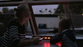 Moeder en kind die toeristische waterreis in avond Amsterdam hebben stock videobeelden