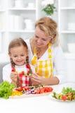 Moeder en kind die voedsel voorbereiden Stock Foto