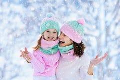Moeder en kind in gebreide de winterhoeden in sneeuw royalty-vrije stock foto