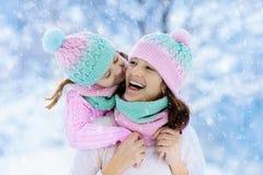 Moeder en kind in gebreide de winterhoeden in sneeuw stock foto's