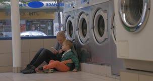 Moeder en kind gebruiken mobiel in de wasserij stock videobeelden