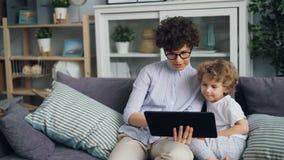 Moeder en kind gelukkige familie gebruikend tablet wat betreft het scherm en thuis sprekend stock footage
