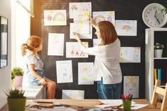 Moeder en kind het meisje hangt hun tekeningen op muur Stock Foto