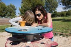 Moeder en kind het spelen met zand bij speelplaats Stock Foto