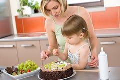Moeder en kind met chocoladecake in keuken Royalty-vrije Stock Afbeeldingen