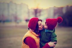 Moeder en kind, omhelzen openlucht op een de winterdag Stock Afbeeldingen