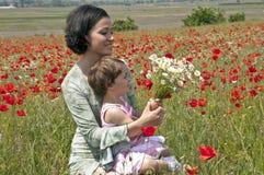 Moeder en kind onder de bloemen Stock Foto