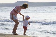 Moeder en kind op een strand stock afbeeldingen