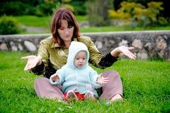 Moeder en kind op gras Stock Afbeeldingen