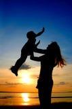 Moeder en kind op zonsondergang Stock Afbeelding