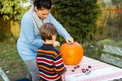 Moeder en kind snijdende pompoen voor Halloween Royalty-vrije Stock Foto