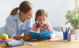 Moeder en kinddochter die thuiswerk doen die en schrijven lezen bij Royalty-vrije Stock Foto's