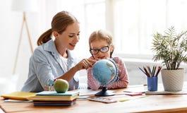 Moeder en kinddochter die thuiswerkaardrijkskunde met bol doen stock foto