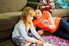 Moeder en kinddochter samen het spelen, bouwt van de aannemer leuk haar zoonsspel stock afbeelding
