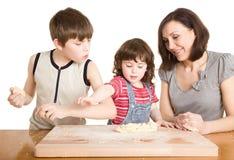 Moeder en kinderen in de keuken die een deeg maakt Stock Afbeeldingen