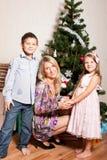 Moeder en kinderen dichtbij een spar Stock Afbeeldingen