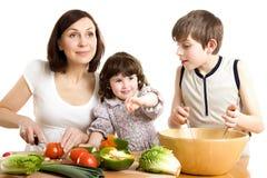 Moeder en kinderen die bij de keuken koken Stock Afbeelding