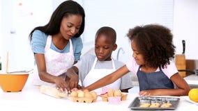 Moeder en kinderen die gebakje maken stock video
