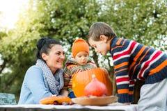 Moeder en kinderen die Halloween-pompoen onderzoeken Royalty-vrije Stock Foto