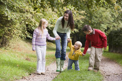 Moeder en kinderen die langs bosweg lopen Stock Foto's