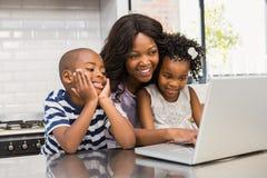 Moeder en kinderen die laptop met behulp van Stock Foto's