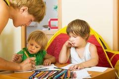 Moeder en kinderen die met potloden spelen Stock Afbeelding