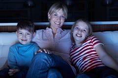 Moeder en Kinderen die op Programma over TV Tog letten Royalty-vrije Stock Fotografie
