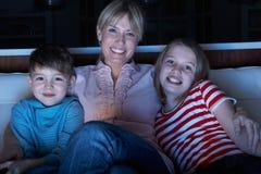 Moeder en Kinderen die op Programma over TV Tog letten Royalty-vrije Stock Foto's