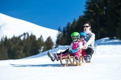 Moeder en kinderen die pret op slee met panoramatic mening van de bergen van Alpen hebben Actief mamma en peuterjong geitje met v royalty-vrije stock fotografie