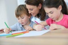 Moeder en kinderen die prettekening hebben stock afbeelding