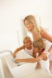 Moeder en Kinderen die Tanden in Badkamers borstelen Stock Foto