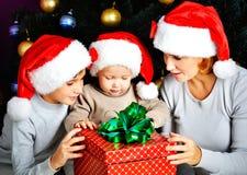 Moeder en kinderen met nieuwe jaargift op de Kerstmisvakantie Stock Foto