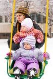 Moeder en kinderen in schommeling in de winter Royalty-vrije Stock Fotografie