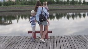 Moeder en kinderengang langs de dijk van de rivier in de zomer stock video